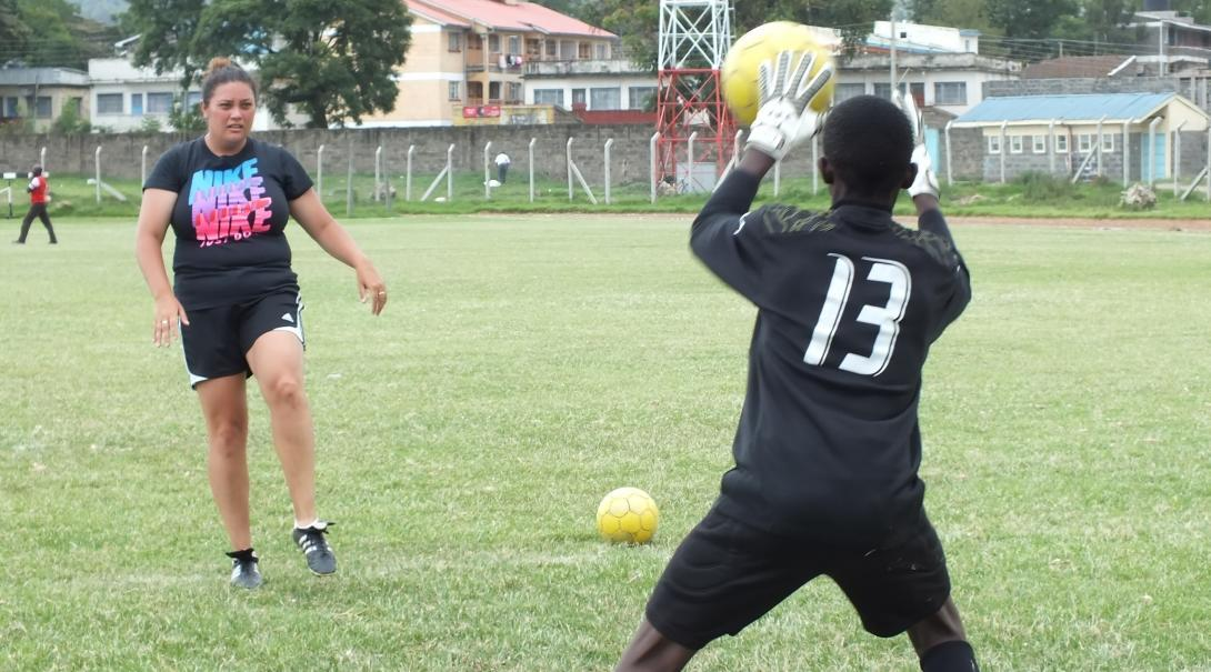 A football player practises defending the goal during volunteer sports coaching in Kenya